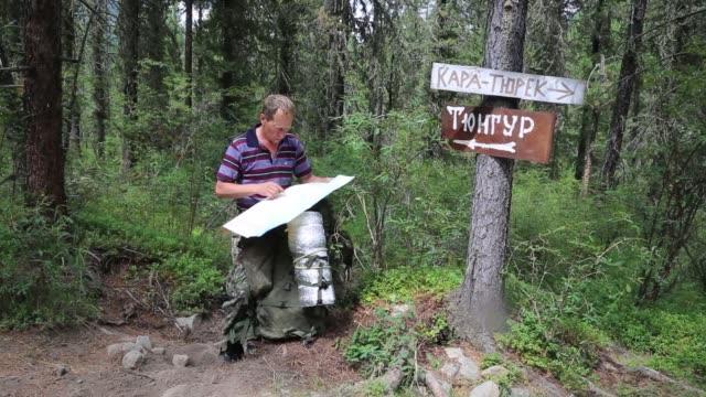 vidéos et rushes de touristique avec une carte près les signes. village de tungur inscriptions, kara turek montagne. - un seul homme d'âge mûr