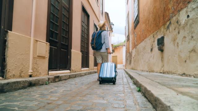 tourist with a suitcase looking for accommodation place - fare una prenotazione video stock e b–roll