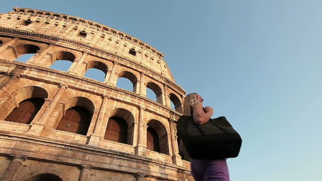 Tourist woman admiring the Coliseum (Colosseo) while passing by it video