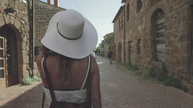 Tourist woman enjoying summer vacations in Italy: walking in small typical town