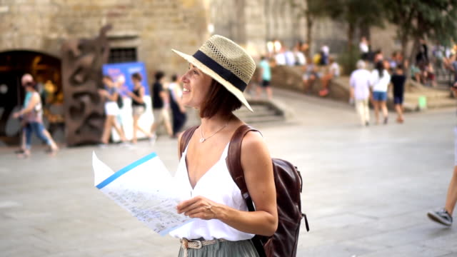 Tourist woman exploring city with map while traveling