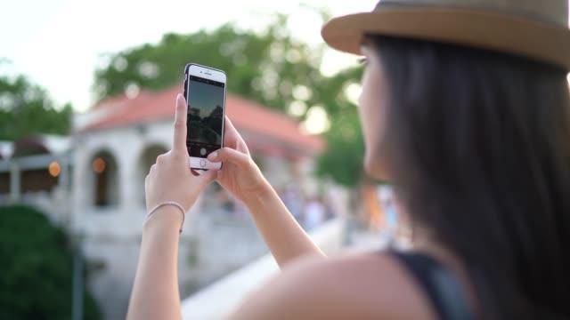 turist kvinna filma sightseings med mobil i dubrovnik gamla stan, kroatien - filma bildbanksvideor och videomaterial från bakom kulisserna