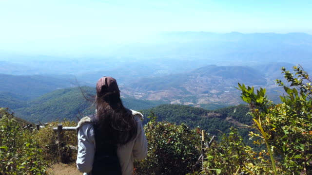 Tourist  woman hiker on mountain top looking at panoramic