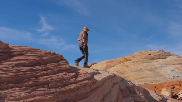 tourist woman hiking down the crest hill with colorful red rocks slow motion 4k - red rock canyon national conservation area video stock e b–roll