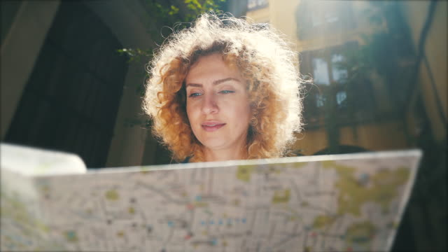 Tourist woman looking on the city map. Young woman looking for new places to visit in Barcelona. She is enjoying a beautiful sunny day, perfect to walk around the city. guidance stock videos & royalty-free footage
