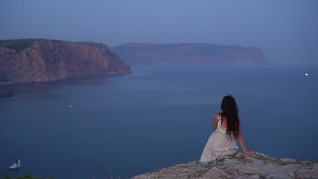 tourist woman outdoor on edge of cliff seashore - wschodnio europejski filmów i materiałów b-roll