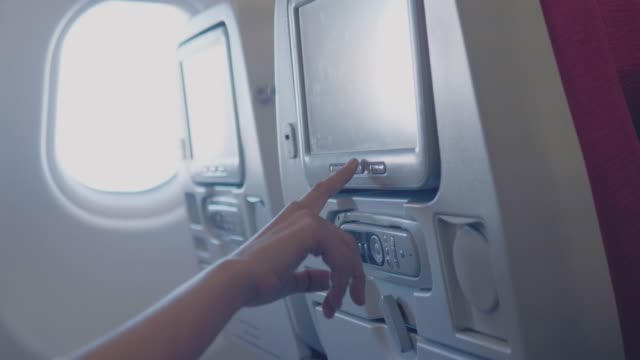 tourist woman sitting near airplane window and using entertainment stuff on the plane at sunset during flight - sedili aereo video stock e b–roll