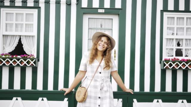 vídeos de stock e filmes b-roll de tourist woman standing near colorful house - aveiro