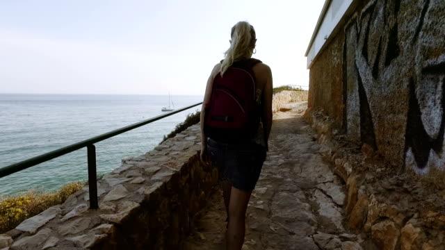 turist kvinna reser till medelhavet land på vårsäsongen. flicka promenad stenvägen väg med havet på en backgorund - stenmur bildbanksvideor och videomaterial från bakom kulisserna