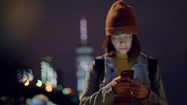 nehri yakınında iskelede cep telefonu kullanan turist kadın. brooklyn köprüsü. - kapüşon stok videoları ve detay görüntü çekimi