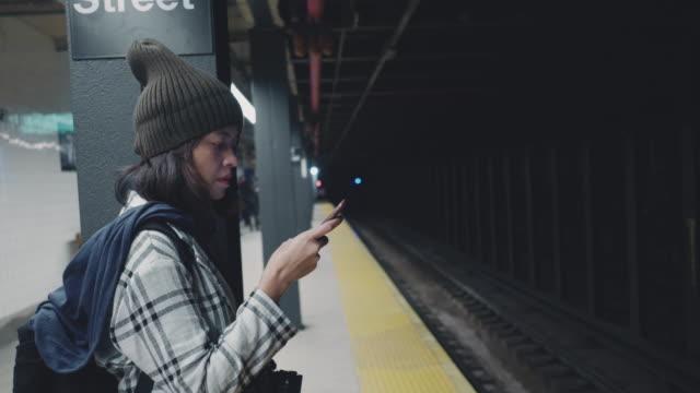 stockvideo's en b-roll-footage met toeristische vrouw te wachten en sms met mobiele telefoons op metro platform - aziatische etniciteit