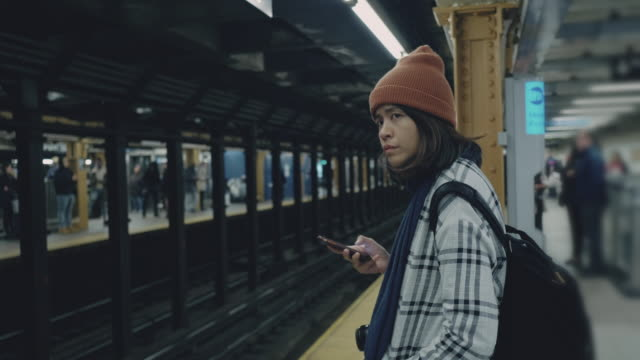 Tourist woman waiting and texting with cell phones on subway platform Asian woman traveler using smartphone and waiting a train in the station at New York City. USA subway station stock videos & royalty-free footage