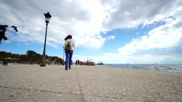vídeos y material grabado en eventos de stock de mujer turista caminar en el paseo marítimo en tesalónica, grecia - espalda humana