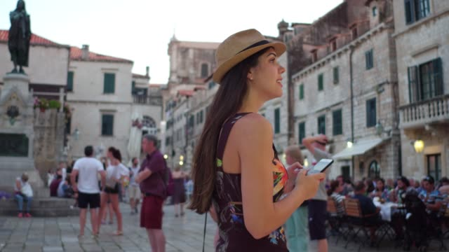 tourist woman walking and discovering the dubrovnik old town, croatia - хорватия стоковые видео и кадры b-roll