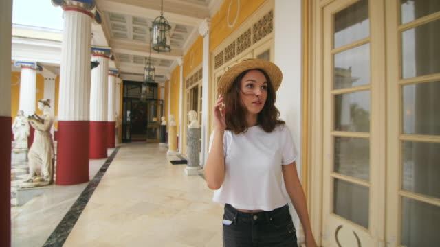Tourist woman walking on column corridor ancient building at summer travel