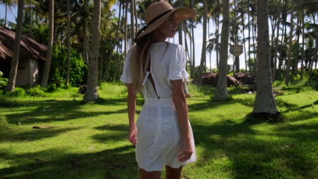 vídeos y material grabado en eventos de stock de mujer turista camina en el jardín tropical - espalda humana