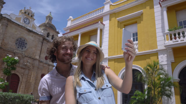 tourist young couple taking a selfie with a smartphone - колумбия стоковые видео и кадры b-roll