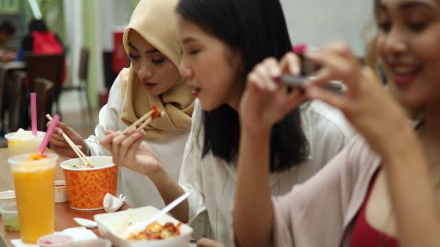 観光クアラルンプールで伝統的な食べ物の写真を撮る若いイスラム教徒の女性 - アジア旅行点の映像素材/bロール