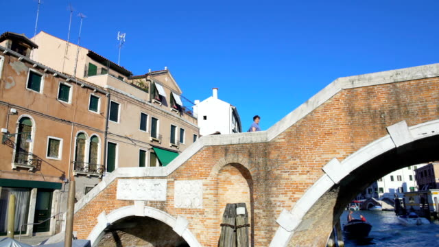 Touristic boat floating under brick bridge in Venice, water transportation, tour video