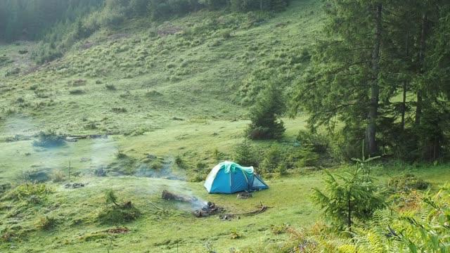 夏のカルパティア山脈の観光のテント。非常に長いショット。ウクライナの自然風景。丘の中腹に緑の芝生、松やもみ覆われています。青いテント近く喫煙を発射します。背景をぼかした写� - 自生点の映像素材/bロール