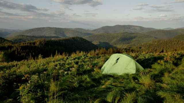 touristic tent in mountains on sunset , wind shakes the grass video