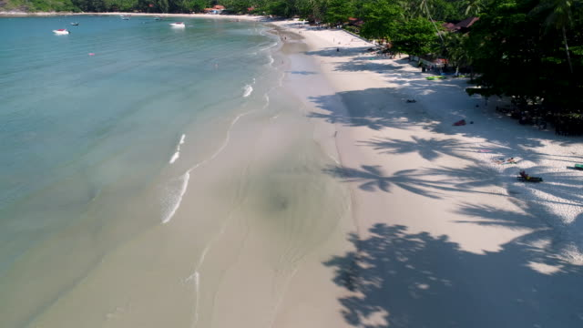 Tourists are resting on a beautiful beach 4k. Cinematic aerial footage. Happy life. Tourists are resting on a beautiful beach. Bathe in the blue ocean, sunbathe, play beach games. Weather is Sunny and Ocean is Blue. Drone footage. lounge chair stock videos & royalty-free footage