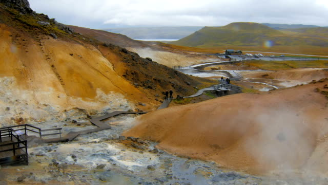 tourists are strolling in Seltun, Krysuvik in Iceland in cloudy wet weather,drop of rain in a camera video