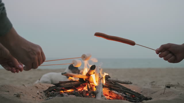 Tourists camping fry sausages, marshmallows over high heat, flame at late beautiful sunset at sea summer, close-up. Mother and son on summer vacation by sea and cooking. Family. Lifestyle. Travel