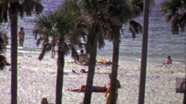 1967: Tourists enjoy relaxing palm tree laden white sand beach. video