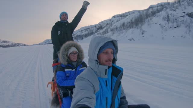 slo mo pov tourists having fun dog sledding in norway - fiordo video stock e b–roll