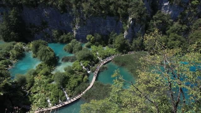 туристов в национальный парк плитвицкие озёра в хорватии - национальный парк плитвицкие озёра стоковые видео и кадры b-roll