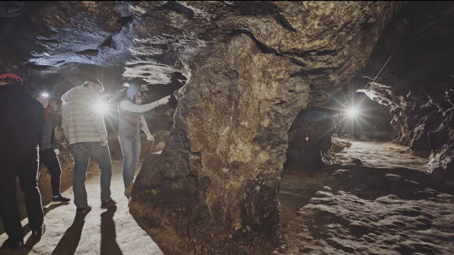 Tourists led by a guide in an underground tunnel