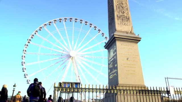 yüksek mısır luksor dikilitaşı, büyük gözlem tekerlek paris bakarak turist - obelisk stok videoları ve detay görüntü çekimi