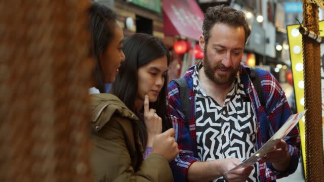 tourists looking at menu in tokyo - turysta filmów i materiałów b-roll