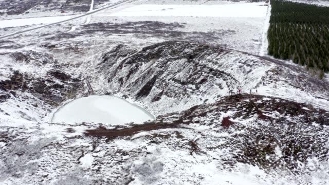 vídeos y material grabado en eventos de stock de los turistas que buscan en el nevado kerid cráter en islandia visto desde el aire - basalto