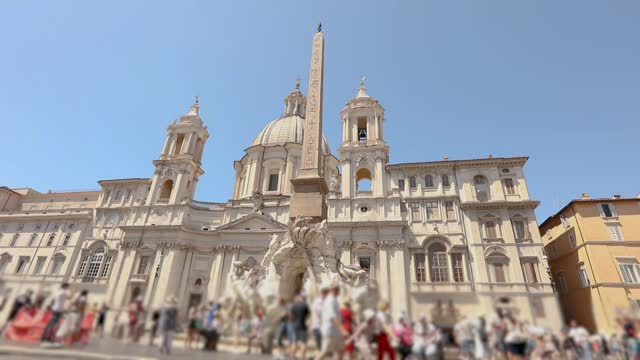 Tourists near Fountain of the Four Rivers on Piazza Navona in Rome Italy