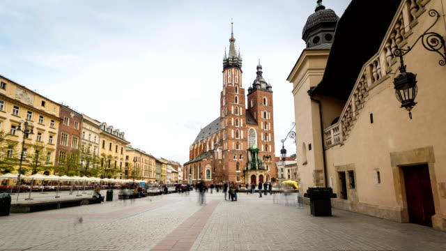 Tourists on Market square with historic church, cloth hall in Krakow, Poland video
