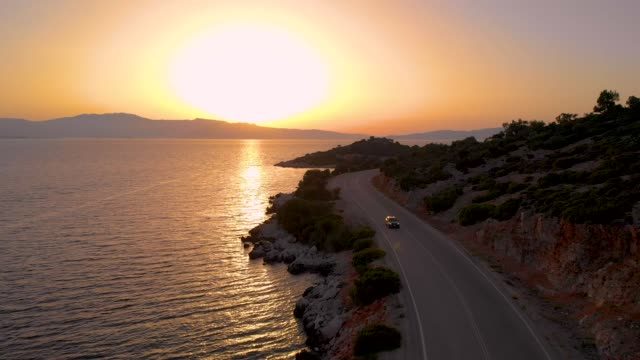 drone: tourists on road trip exploring the mediterranean island at sunset. - sunset stock videos & royalty-free footage