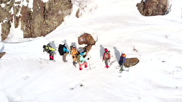 tourists point ski poles in the direction in which they will be sent further. Above them flies the quadcopter and remove them from the height of bird flight aerial