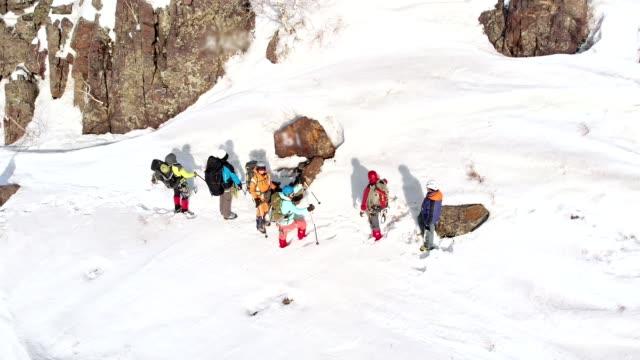 관광객 들은 더 많은 것을 보낼 방향으로 스키 폴을 가리킵니다. 그들은 쿼드 콥 터를 날아와 조류 비행 공중의 높이에서 그들을 제거 - mountain top 스톡 비디오 및 b-롤 화면