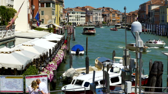 Tourists standing on pier and looking at city map, Grand Canal, cafe in Venice video