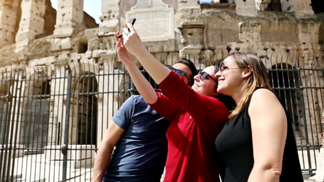 Tourists taking a selfie in front of the Coliseum, Rome video