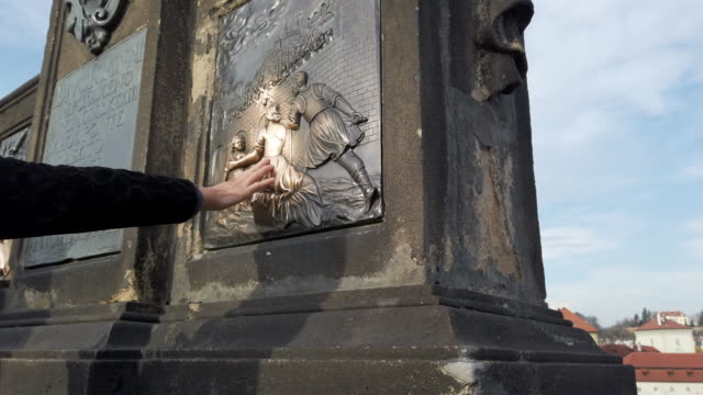 Tourists Touching the Reliefs at the Statue of St. John of Nepomuk on Charles Bridge