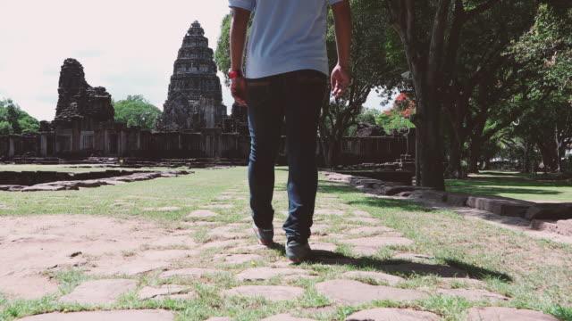 vídeos de stock, filmes e b-roll de turistas que visitam a bela do parque histórico de phimai, tailândia - phimai