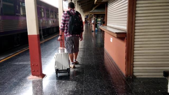 tourists walk dragging luggage in the train station. work and travel concept. - intercity filmów i materiałów b-roll