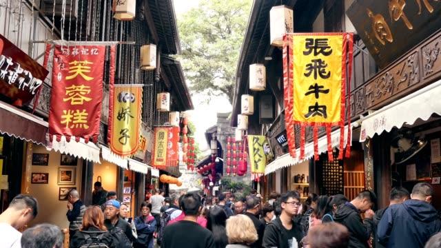 vídeos y material grabado en eventos de stock de los turistas que caminan en la antigua tradicional en la calle peatonal en el barrio chino de chengdu - aldea