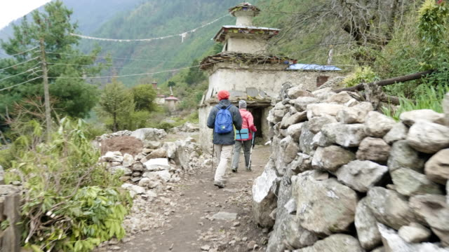 tourists walking in nepalese village prok, trek around mountain manaslu, nepal. - mustang video stock e b–roll