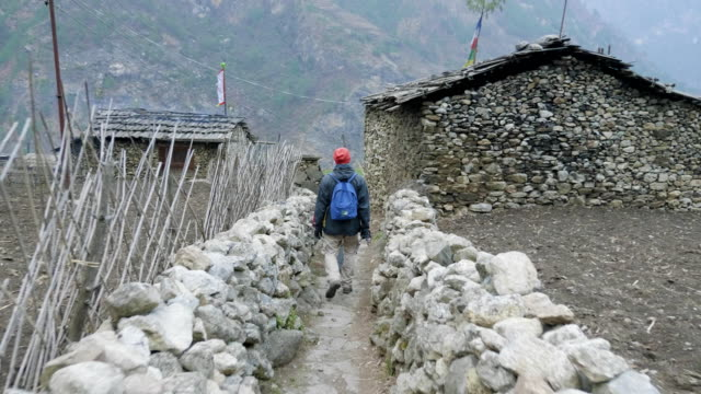 tourists walking in nepalese village prok, trek around mountain manaslu, nepal. - мустанг стоковые видео и кадры b-roll