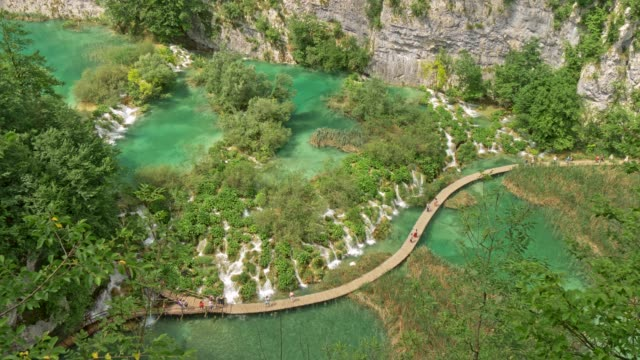 tourists walking the boardwalk among waterfalls and cascades and green flora and turqouise lakes in plitvice lakes national park, croatia. uhd - национальный парк плитвицкие озёра стоковые видео и кадры b-roll