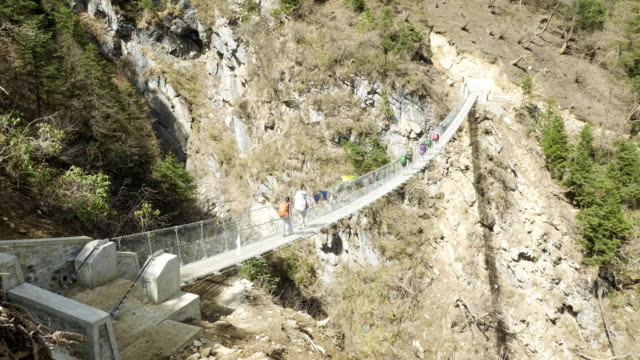 Tourists with the guide on the suspension bridge in Himalaya, Nepal. Tourists with the guide on the suspension bridge in Himalaya, Nepal suspension bridge stock videos & royalty-free footage